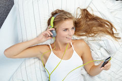 Blonde woman lying on bed while listening music Stock Photos