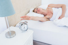 Blonde woman lying in bed reaching for alarm clock Royalty Free Stock Images
