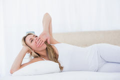 Blonde woman lying in bed yawning Royalty Free Stock Photography