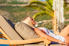 Blonde woman lying on deckchair, enjoying summer holidays. Royalty Free Stock Images