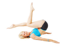 Blonde woman lying on her back doing gymnastics Stock Photos