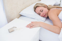 Blonde woman lying motionless in bed after overdose Stock Photos