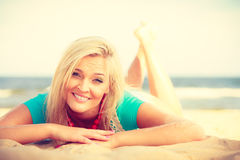 Blonde woman lying on sand. Royalty Free Stock Photography