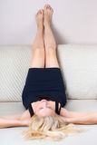 Blonde woman lying on sofa Stock Photo