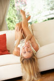 Blonde Woman Lying Upside Down On Sofa Royalty Free Stock Photos