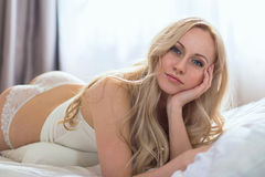 Blonde woman lying on the white bed Stock Photography