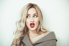 Blonde woman making face expressions. Blonde woman with long hair standing against white wall making face expressions Royalty Free Stock Photography
