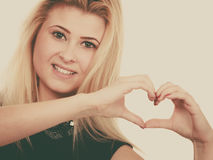 Blonde woman making heart symbol with hands. Gestures and human reactions concept. Coquet blonde woman making heart symbol with hands Royalty Free Stock Images