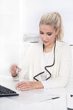 Blonde woman is making her nails at desk. Stock Photography