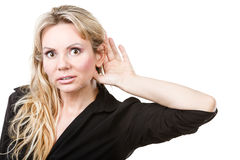 Blonde woman making listening gesture Royalty Free Stock Image