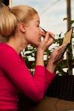 Blonde woman making makeup to herself, applying eyeshadows on ey Royalty Free Stock Photos