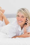 Blonde woman making a phone call lying on bed Stock Image