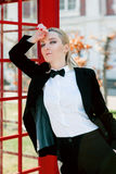 Blonde woman in man black suit near red telephone box. Portrait of stylish beautiful blonde woman in man black suit near red telephone box Royalty Free Stock Images