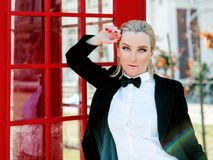 Blonde woman in man black suit near red telephone box. Portrait of stylish beautiful blonde woman in man black suit near red telephone box Stock Images