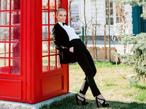 Blonde woman in man black suit near red telephone box. Portrait of stylish beautiful blonde woman in man black suit near red telephone box Stock Photos