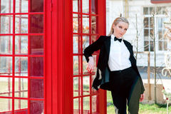 Blonde woman in man black suit near red telephone box. Portrait of stylish beautiful blonde woman in man black suit near red telephone box Royalty Free Stock Photo