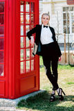 Blonde woman in man black suit near red telephone box. Portrait of stylish beautiful blonde woman in man black suit near red telephone box Royalty Free Stock Photography
