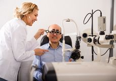 Blonde woman and a man pensioner ophthalmologist check eyesight in clinic. Voluptuous blonde women and a men pensioner ophthalmologist check eyesight in clinic Stock Photography