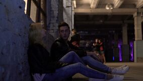 Blonde woman and man sitting near wall and talking, after-party, night life. Stock footage stock video