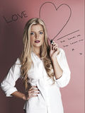 Blonde woman with marker pen drawing hearts Stock Image