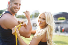 Blonde woman measure mans biceps by yellow measuring tape. Blonde women measure mans biceps by yellow measuring tape in nature Royalty Free Stock Photo