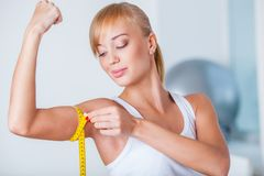 Blonde woman measuring biceps. Young beautiful blonde woman measuring her biceps with tape stock photography