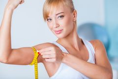 Blonde woman measuring biceps. Young beautiful blonde woman measuring her biceps with tape stock photo