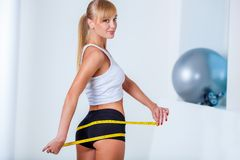 Blonde woman measuring her buttocks. Young beautiful blonde woman measuring her buttocks with yellow tape Stock Image