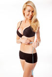 Blonde woman measuring her stomache. Happy blonde woman measuring her waist on white Stock Photos