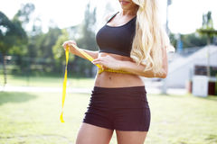 Blonde woman measuring waist circumference Royalty Free Stock Photography