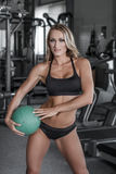Blonde woman with medicine ball in gym royalty free stock photo