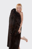 Blonde Woman With A Mink Coat. A blonde woman is naked underneath her mink coat and is smiling happily, surprising her husband Royalty Free Stock Images