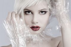 Blonde woman model in plastic. Beautiful girl model with plastic around her neck. Toned and professional makeup Stock Images