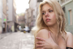Blonde woman with naked shoulders at the street. Pretty woman with naked shoulders at the street Royalty Free Stock Photography
