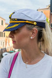 Blonde woman in navy cap. Beautiful blonde woman wear souvenir V Royalty Free Stock Photography