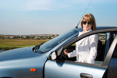 Blonde woman near blue car Royalty Free Stock Image