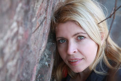 Blonde woman near a wall with lians on the face Royalty Free Stock Photos