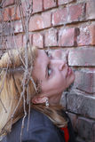 Blonde woman near a wall with lians on the face Royalty Free Stock Photo