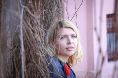 Blonde woman near a wall with lians on the face Royalty Free Stock Photography