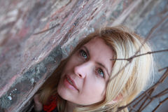 Blonde woman near a wall with lians Stock Photo
