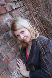 Blonde woman near wall and lians Stock Image