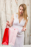 Blonde woman opening a gift bag while looking at camera Royalty Free Stock Photo