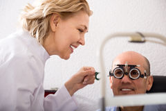 Blonde woman ophthalmologist and  smiling man pensioner check eyesight in clinic Stock Image