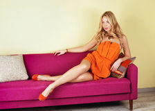 blonde woman in a orange dress on purple couch Stock Image