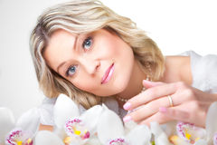 Blonde woman with orchid on white Stock Photography