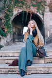 Blonde woman outdoors city walk fashion lifestyle look. Fashion look girl model travel in coat sit on stairs in autumn Stock Image