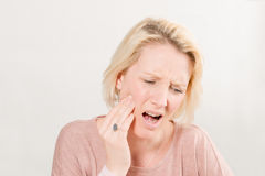 Blonde Woman in Pain Touching Cheek Royalty Free Stock Photography