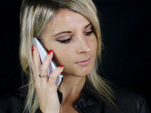 Blonde woman passing a phone call. On a black background royalty free stock images