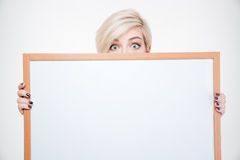 Blonde woman peeking from blank board Stock Photo