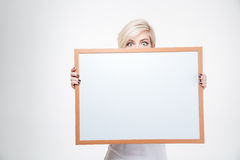 Blonde woman peeking from blank board Royalty Free Stock Images